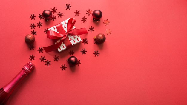 Christmas banner with sparkling wine, gift, red holiday decor on red space