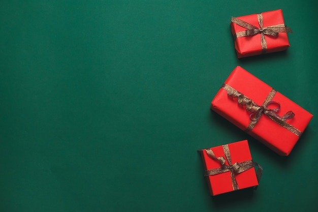 Christmas banner. xmas background design with craft red gift box with gold ribbon on green background