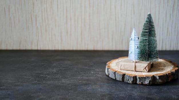 クラフトギフトボックスと木製の円錐形のおもちゃのクリスマスツリーとクリスマスバナークリスマス最小限の背景
