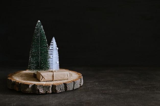 クラフトギフトボックスとコーンおもちゃのクリスマスツリーとクリスマスバナークリスマス最小限の暗い背景