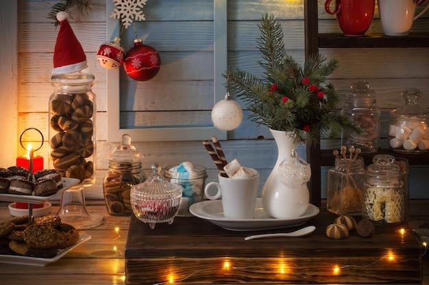 ヴィンテージスタイルの青い木製の背景にクッキーとお菓子とクリスマスバーカカオ装飾