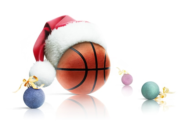 クリスマスバスケットボール。白い背景の上のサンタ帽子クリスマスおもちゃのバスケットボールボール。孤立