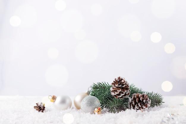 Рождественская безделушка на еловой ветке с шишкой и блестящим фоном
