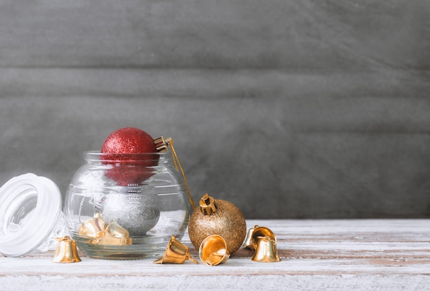 Christmas baubles and bell on white wood table background