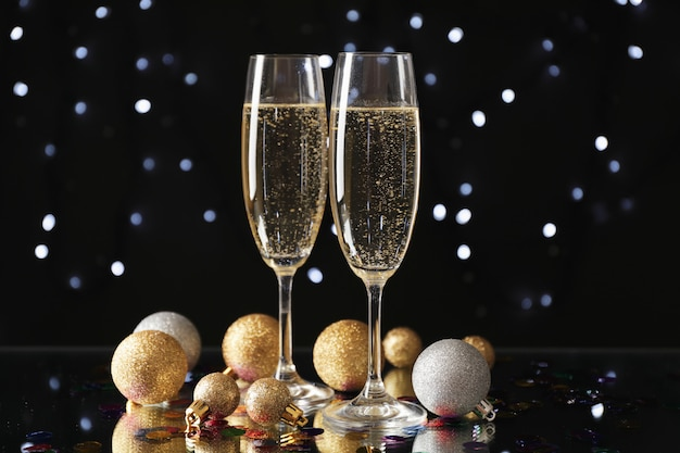 Christmas baubles and champagne glasses on blurred space, copy space