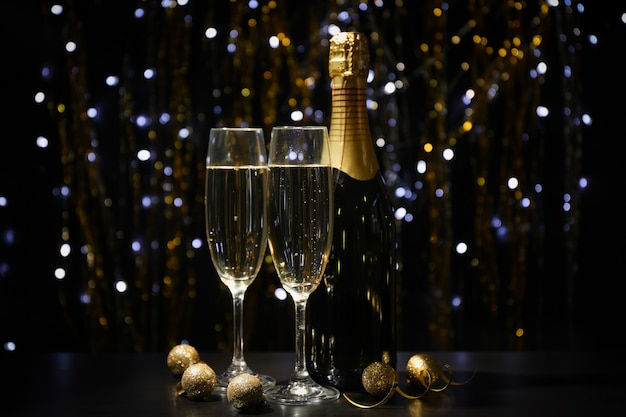 Christmas baubles, champagne glasses and bottle on blurred space, copy space
