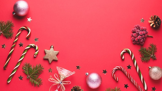 Christmas baubles, golden decorations, candy canes, pine tree, cones and confetti frame on red background. festive christmas border with golden elements. flat lay, top view, copy space