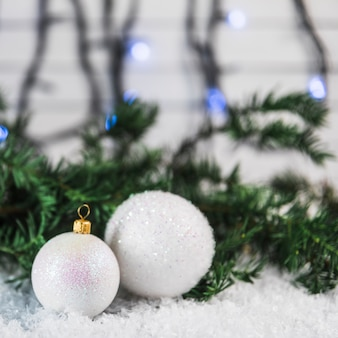 Christmas baubles near fir twig on snow