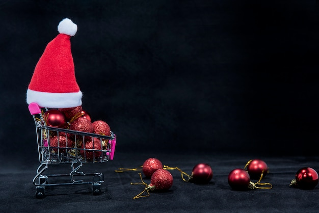 Christmas baubles on small shopping cart with santa hat