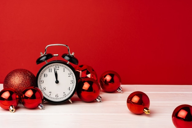 Christmas baubles with alarm clock on red