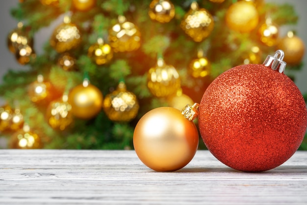 Christmas baubles on wooden table against decorated christmas tree blurred background