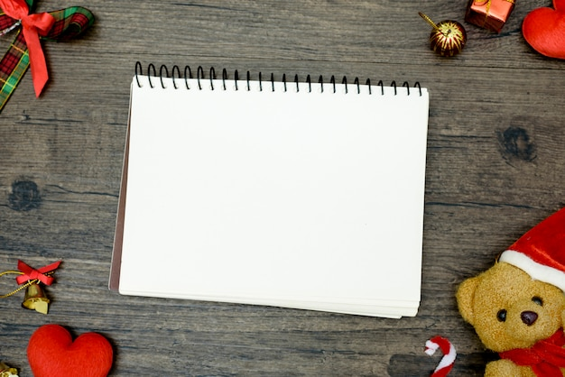 Медведь рождества и пустая книга с взгляд сверху и космос экземпляра на коричневом деревянном столе. рождественский фестиваль концепции фон