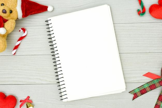 Медведь рождества и белая книга с взгляд сверху и космос экземпляра на белом деревянном столе. концепция праздника рождества.