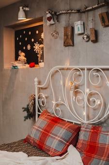 ロフトスタイルのクリスマスの寝室の装飾、コンクリートグレー、壁に掛かっている贈り物とスティック。