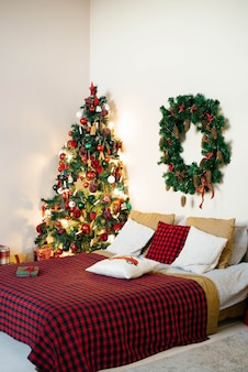 Christmas bedroom interior in white and red colors. double bed with plaid blanket and christmas tree