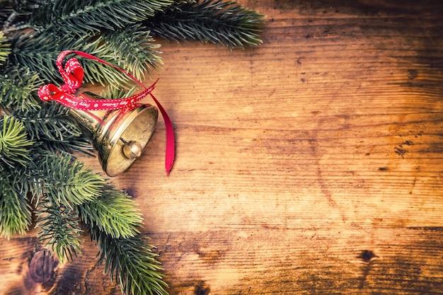 나무 보드에 텍스트 해피 크리스마스와 함께 크리스마스 벨 전나무 레드 리본