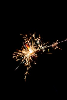 Рождественский бенгальский огонь сверкает на черном фоне.