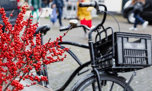 クリスマスベリーのヒイラギまたはモチノキの小枝と伝統的なオランダの自転車が外にあります。屋外のクリスマスの装飾とアムステルダムの都会の冬の街並み。ヨーロッパの年末年始。