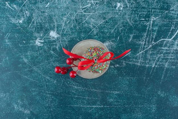 Un ornamento di bacche di natale e un lecca-lecca su un pezzo di legno su sfondo blu. foto di alta qualità
