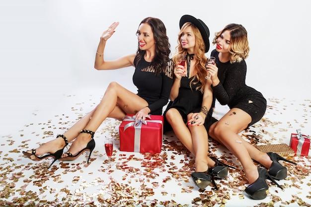 Festa di natale o di compleanno. tre belle donne sedute sul pavimento e bere cocktail. i migliori amici scompattano i regali. coriandoli scintillanti dorati. sfondo bianco. acconciatura ondulata.