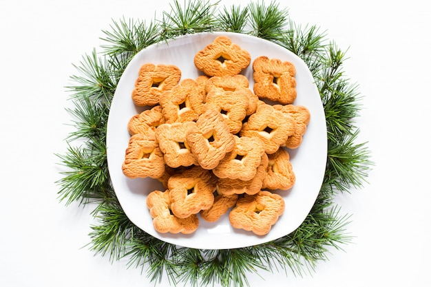 Christmas biscuits on a dish on white background