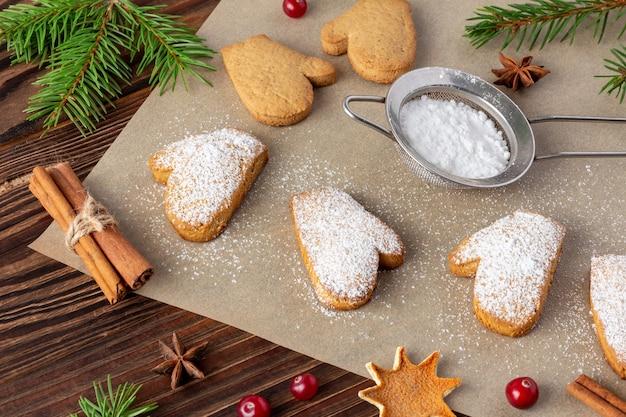Рождественское печенье на бумаге для выпечки с сахарной пудрой и палочками корицы крупным планом