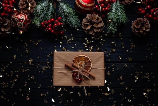 クリスマスの黒い背景、クリスマスボール、枝、クラフトギフトの装飾品。新年2021ソフトセレクティブフォーカス。