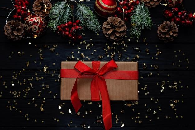 クリスマスの黒い背景、クリスマスボール、枝、赤いリボンの装飾ギフト。新年2021ソフトセレクティブフォーカス。