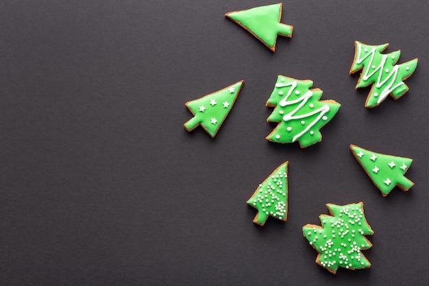 Рождественский черный фон с пряниками в форме елки с глазурью