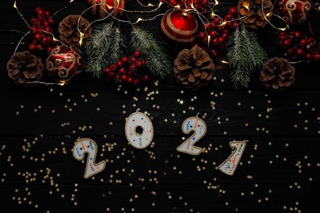 ライト付きの碑文2021とクリスマスの黒い背景。クリスマスボール、枝、ギフト用の装飾品。新年2021ソフトセレクティブフォーカス。