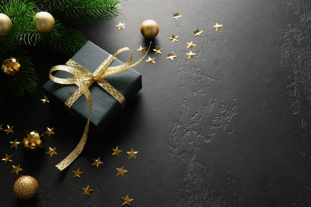 Christmas black gift with decorative golden ribbon on black surface.