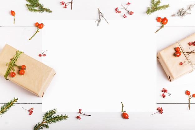 Рождественская пустая открытка в рамке из еловых веток с красными ягодами, подарочными коробками и шишками