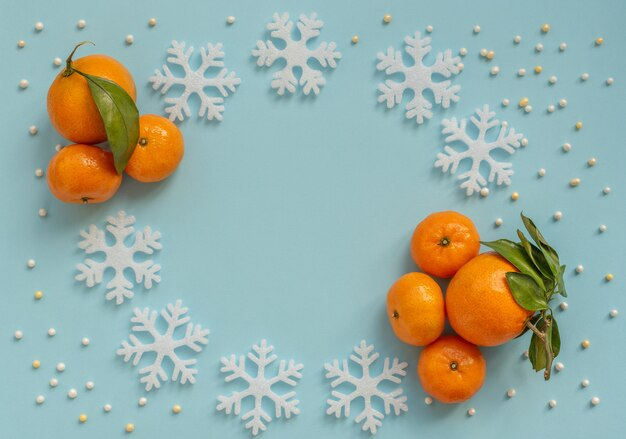 Christmas blue background with orange tangerines and white snowflakes. new year greeting card. flat lay style.