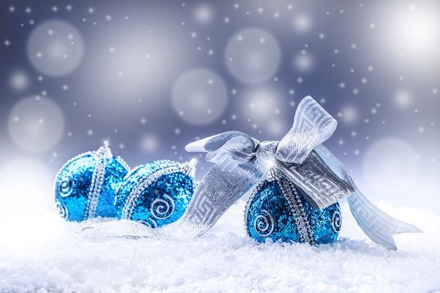 Рождественские синие шары и серебряная лента снег и космический абстрактный фон.