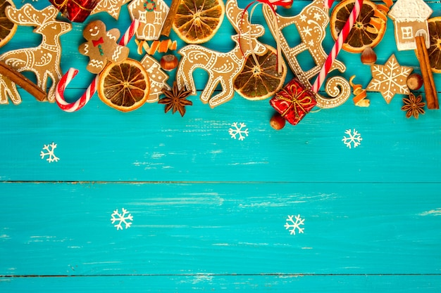 Christmas blue wooden background with gingerbread, cinnamon, orange and balls.