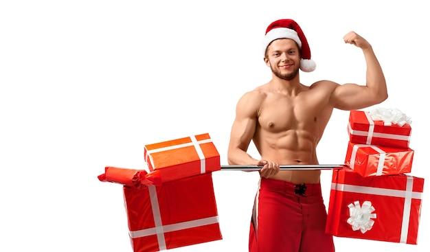 クリスマスのボディービル。白で隔離のボディービルのポーズで彼の筋肉を披露するプレゼントとバーベルを保持しているサンタクロースの帽子をかぶっている裸の破れた男。 2018、2019。