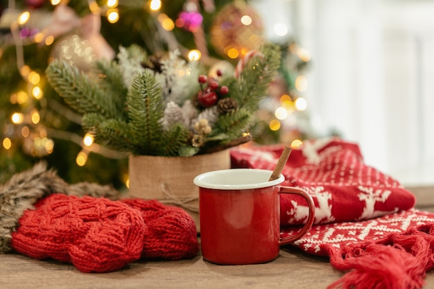 Christmas bokeh background with red gloves, red scarf and red cup of hot chocolate on wood table.