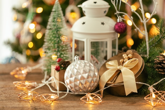 Christmas bokeh background with xmas gift box, lantern, star blinker, bauble and pine cones.