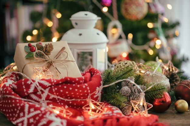 Christmas bokeh background with xmas gift box, scarf, lantern, star blinker, bauble and pine cones.