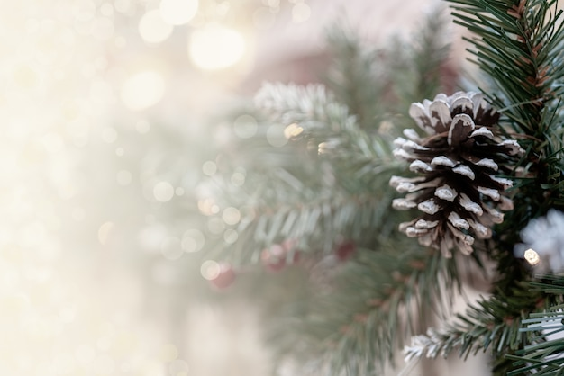 Christmas bokeh effect background with pine branches, cones, and space for inscription