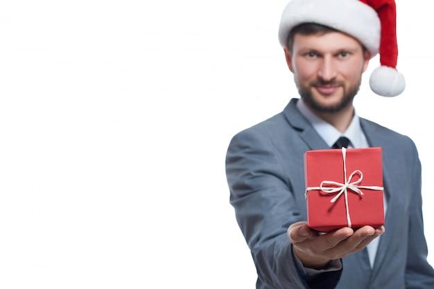 Рождественский бонус. селективный акцент на небольшой красный рождественский подарок молодой предприниматель держит.