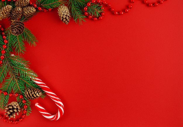 Christmas border composition with candy cane on red background.