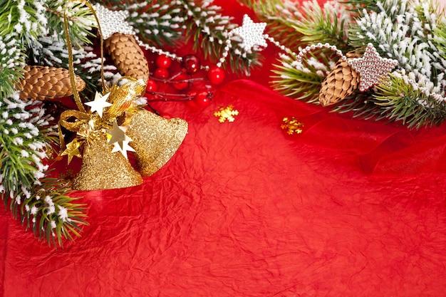 Рождественская граница из ветки и украшения на фоне красной бумаги