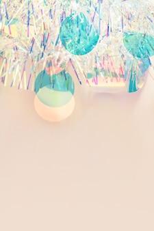 복사 공간이 있는 파스텔 베이지색 배경에 크리스마스 테두리 무지개 빛깔의 반짝이 화환.
