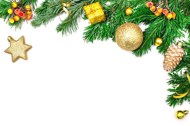 白い背景で隔離のクリスマスの境界線。緑のトウヒの枝、黄色のボール、コーン、星の形でクリスマスの装飾。お祝いのコンセプト。モックアップ