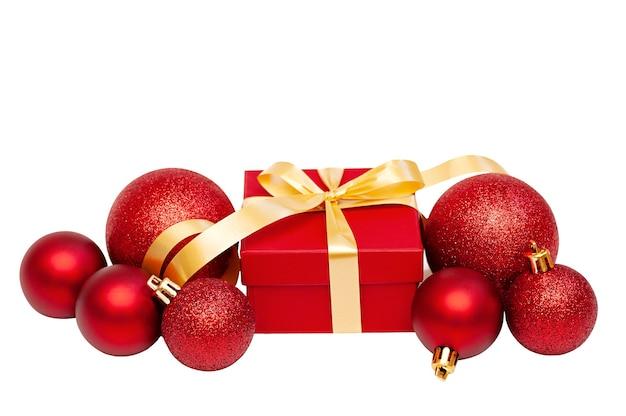 Рождественская граница из красных украшений и подарочной коробки на белом фоне
