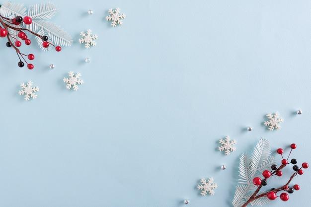 青い表面に雪片と赤い実で作られたクリスマスの境界線
