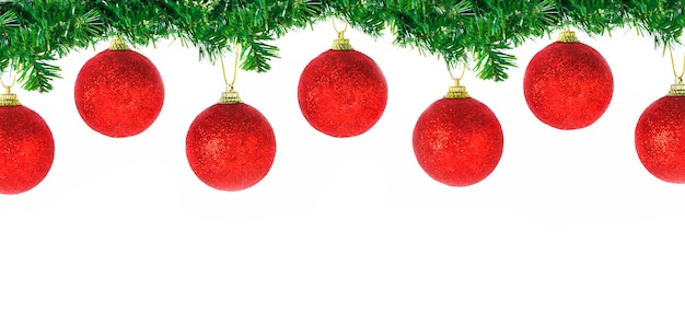 Рождественский бордюр из хвойных еловых веток с висящими красными шарами на белом фоне