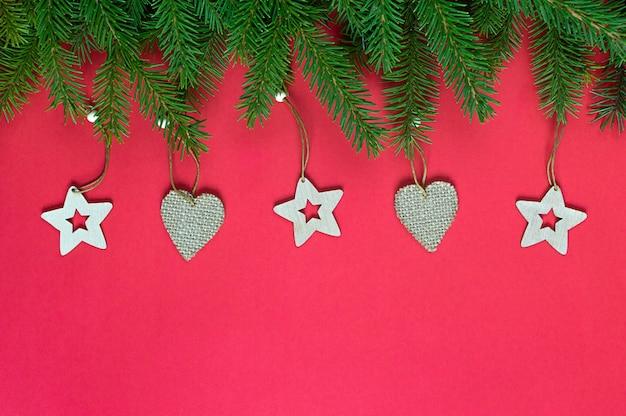 Рождественская граница с еловыми ветками и деревянными елочными игрушками на красном с копией пространства. новогодняя открытка