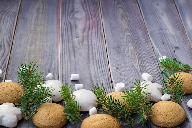 Christmas border with gingerbread, marshmallow and branch of fir tree.